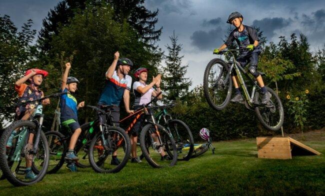 Merlin Lippmann (rechts) springt im heimischen Garten mit dem Fahrrad über eine selbstgebaute Sprungschanze aus Holz. Mutter Nikola May, Stiefvater Mirko May sowie die Geschwister Malik (7) und Fee (10, von rechts) jubeln dem Zwölfjährigen zu, der inzwischen zahlreiche Tricks beherrscht.