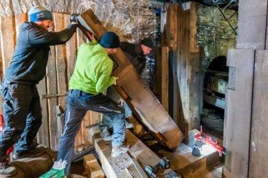 Patrick Einenkel, Nico Wagener und Sebastian Geier (v. l.) beim Einbau einer aus vier Eichenholz-Segmenten bestehenden neuen Säule des Hammergestells.
