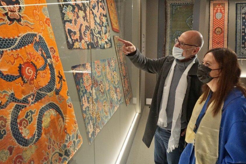 Jochen Wolf und Julia Endemann schauen sich die ausgestellten tibetischen Teppiche der neuen Sonderschau im Museum auf Schloss Voigtsberg in Oelsnitz ganz genau an.