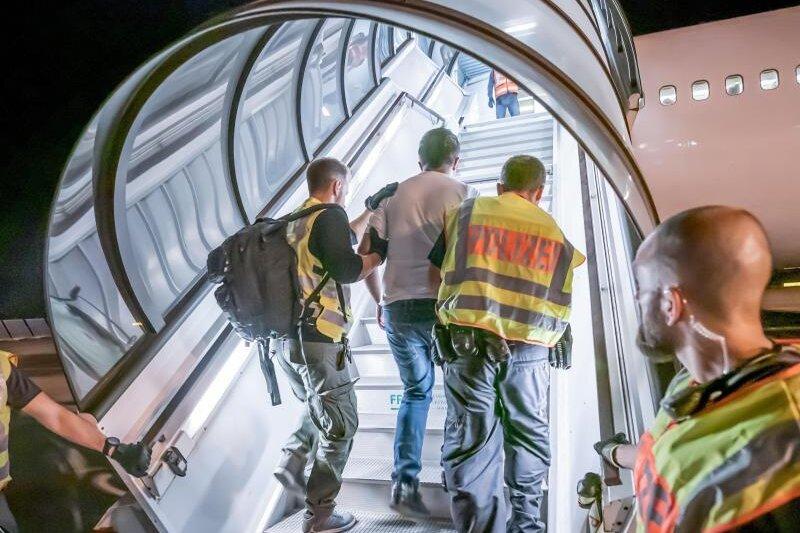 Das Archivfoto aus dem Jahr 2019 zeigt Polizeibeamte, die einen Afghanen bei einer Abschiebung auf dem Flughafen Leipzig-Halle in ein Charterflugzeug begleiten.