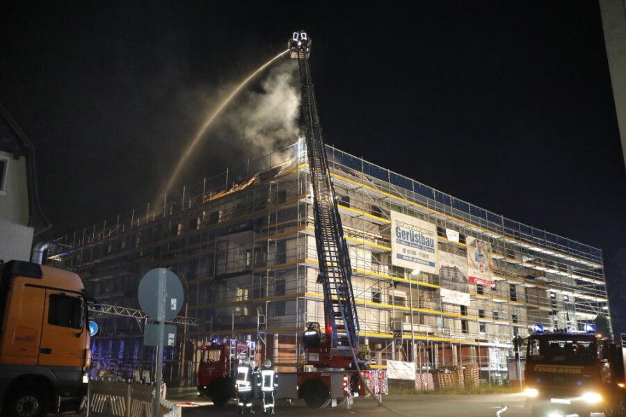 Rohbau eines Wohn- und Geschäftshauses brennt