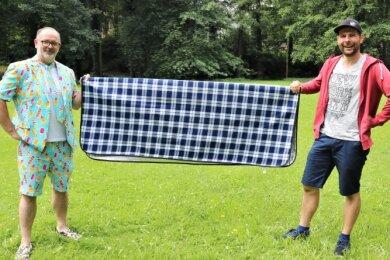Manuel Grießbach (rechts), der Chef des Gewerbe- und Festvereins Flöha, sowie Vereinsmitglied Daniel Ivandic haben schon einmal zur Probe eine Picknickdecke im Baumwollpark ausgebreitet.