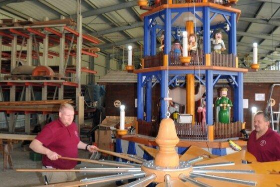 Die Firma Erzgebirgische Holzkunst bereitet einen aufgebaut 7,50 Meter hohen Pyramidenneubau für den Versand vor - im Bild Tobias Fritzsch und Matthias Schiebold (v. l.) am Flügelrad.