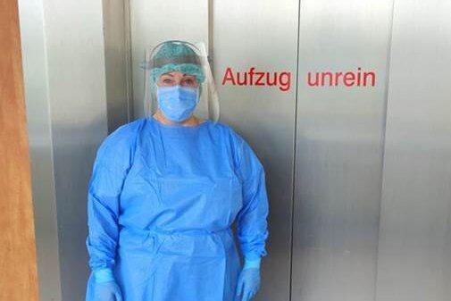 """Eine Stationsschwester in voller Schutzkleidung des Kreiskrankenhauses Stollberg vor einem Patientenaufzug, welcher als """"unrein"""" definiert ist und nur für Covid-19-Patienten in Betrieb genommen wird."""