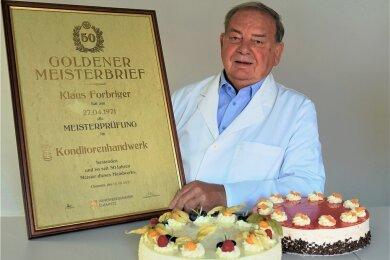 Konditormeister Klaus Forbriger mit seinem Goldenen Meisterbrief und zwei leckeren Torten aus der Produktion von Forbriger Backwaren: Gin und Blutorange.