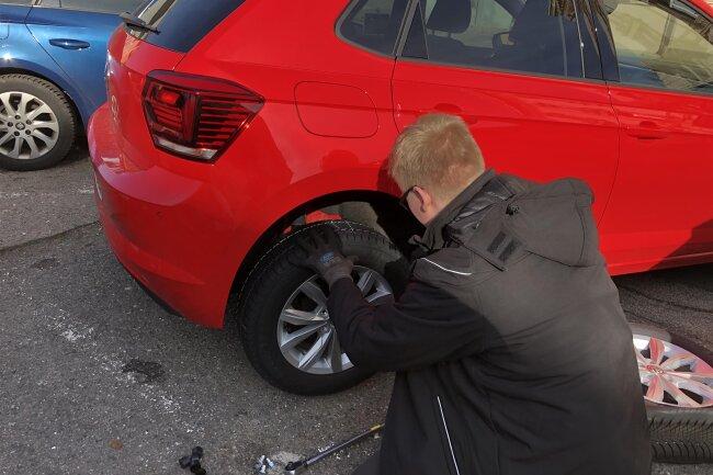 Ein Autofahrer in der Saarstraße beim Wechseln eines zerstochenen Reifens.