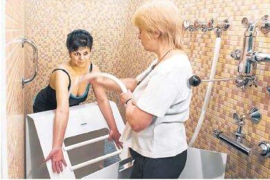 Bildtext: Das kalte Plätschern auf der Haut war für Cornelia Künzer (l.) aus Hoyerswerda zunächst ein kleiner Schock. Doch inzwischen genießt die 39-Jährige ihre Kneippschen Güsse bei Bademeisterin Annegret Herschel. Diese Form der Hydrotherapie gehört zur Behandlung, die sie während ihrer Reha in der Bad Schandauer Kirnitzschtalklinik verordnet bekommen hat. Die Kur wurde nach einer Wirbelsäulen-OP notwendig.