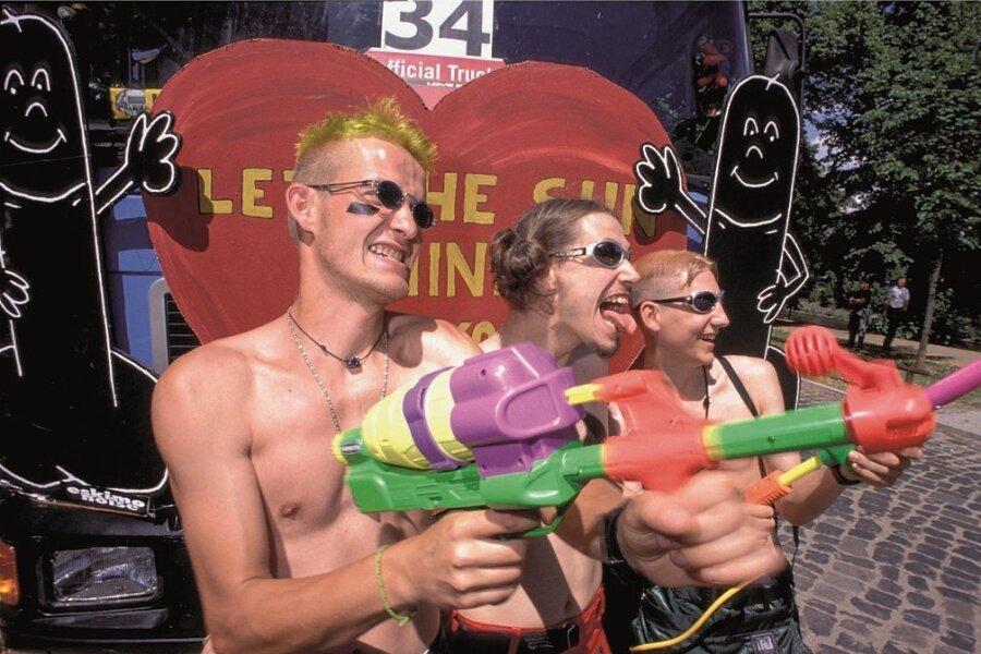 Loveparade: Junge Männer mit nacktem Oberkoerper halten große Wasserpistolen in der Hand und freuen sich.