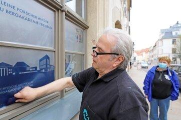 Andreas Kretzschmar bringt die Folien an die Fenster des neuen Regionalbüros der Kleinen Forscher an, hinten Koordinatorin Kathrin Häußler.