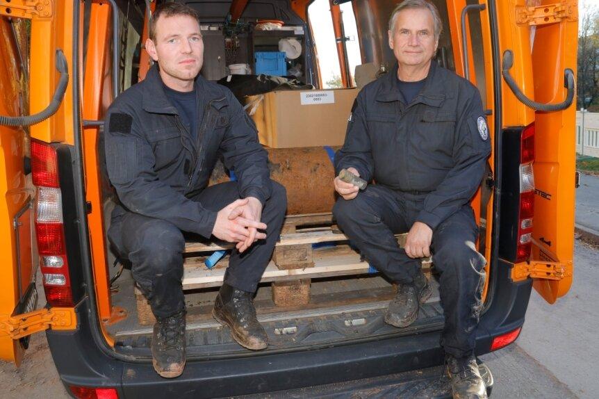 Auszubildender Kai Petrich (links) hat die Bombe unter Aufsicht von Jörg Lange (rechts) entschärft. Sie liegt hinter ihnen im Transporter.