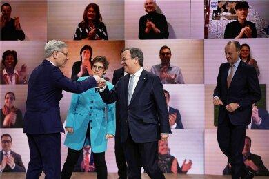 Der neue Parteivorsitzende Armin Laschet (2. v. r) nimmt beim digitalen Bundesparteitag der CDU nach seiner Wahl die Glückwünsche des unterlegenen Norbert Röttgen (l.) entgegen. Dahinter die scheidende Vorsitzende Annegret Kramp-Karrenbauer, rechts der unterlegene Friedrich Merz.