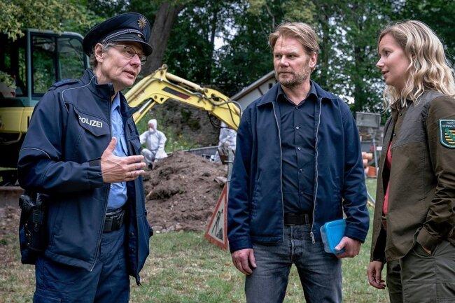 Ortspolizist Rainer Wagner (Thomas Bading, l,) unterrichtet Kommissar Robert Winkler (Kai Scheve, M.) und Försterin Saskia Bergelt (Teresa Weißbach, r.) über den Leichenfund an der Burg.