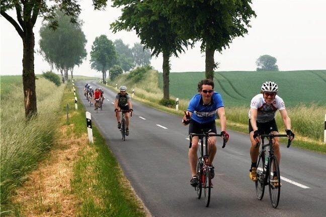 Die Autoschlange hinter Radfahrern