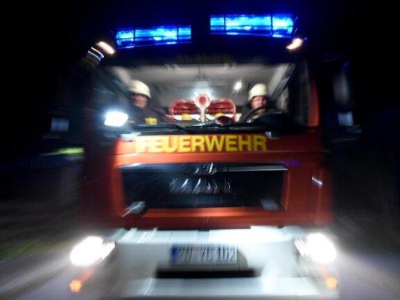 Männer der Feuerwehr sitzen in einem Löschfahrzeug.