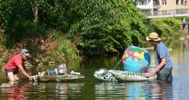 Mit einem Krokodil und einer Schildkröte aus Plastik wollen Winfried Schiller (l.) und Werner Steffens an der Brückenstraße auf Müll in der Chemnitz aufmerksam machen. Dort wurden kürzlich Warnbaken in den Fluss geworfen, die das nahe Kunstwerk der Gegenwarten-Ausstellung schützen sollten.