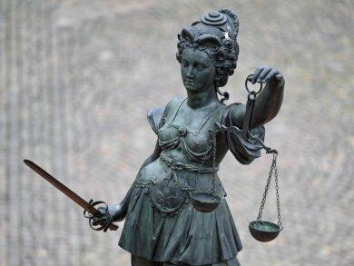 Die Statue der Justitia steht mit einer Waage und einem Schwert in der Hand.