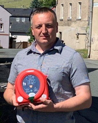 Bad Brambachs Bürgermeister Maik Schüller mit dem Defibrillator am Feuerwehrhaus Schönberg.