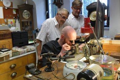 Seit 65 Jahren betreibt Familie Gläser in der Freiberger Burgstraße Uhrmacherwerkstatt und Geschäft, nun in zweiter Generation. Im Bild schauen Geschäftsgründer Johannes Gläser (Mitte) und der jetzige Inhaber Holm Gläser Uhrmacher Richard Schade über die Schulter.