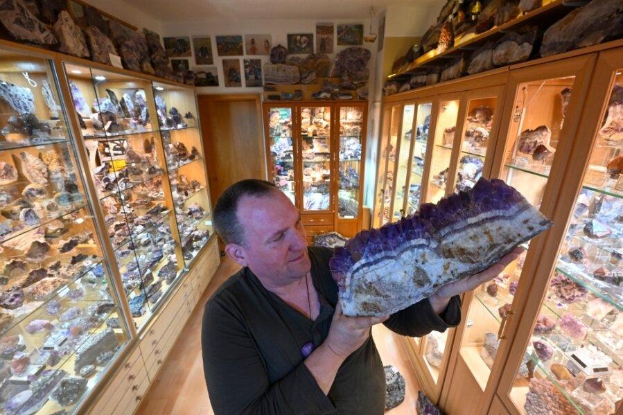 Sammler Jens Häusler inmitten seiner Amethyste in seiner Chemnitzer Wohnung. In seinen Händen hält er ein rund 15 Kilo schweres Exemplar.