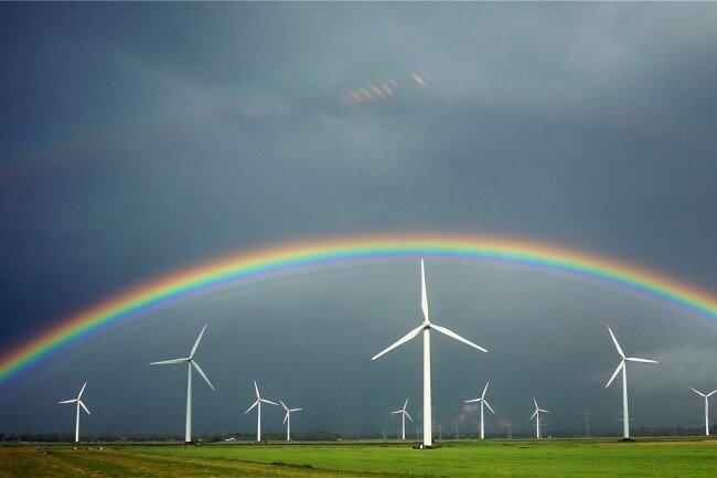 Ein Regenbogen spannt sich bei Wilster in Schleswig-Holstein über Windkraftanlagen. Die schwarz-rote Koalition hat sich auf eine Reform für einen schnelleren Ausbau von Ökostrom verständigt.