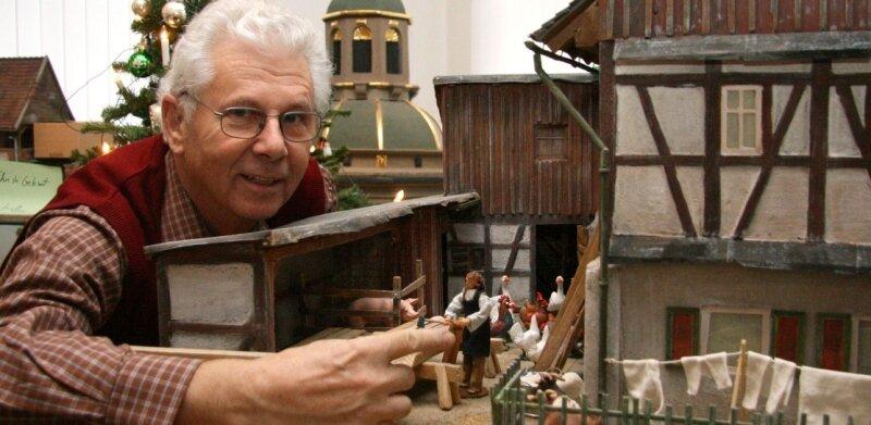 """<p class=""""artikelinhalt"""">Norbert Kühnel am Modell eines Bauernhofes aus Niederalbertsdorf, eine Station des Krippenweges. </p>"""