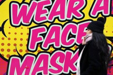 Eine Frau ohne Mund-Nasen-Schutz geht an einem Bild vorbei, das zum Tragen einer Mund-Nasen-Bedeckung auffordert.