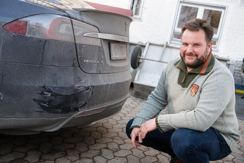 Retter Manfred Kick am demolierten Heck seines Teslas.