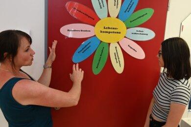 Zu Lebenskompetenzen hat Schulsozialarbeiterin Mary Köhler (l.) eine Blume gestaltet. Diese Kompetenzen will sie den Schülern der Oberschule Zschorlau wie der zwölfjährigen Annika Schwarz vermitteln.