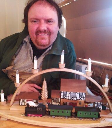 Roman Naumann mit seiner neuesten Kreation - einem Schwibbogen mit Eisenbahn.