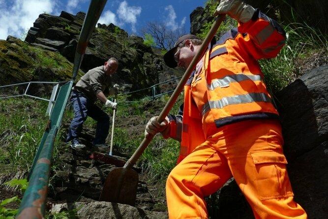 In der Wolfsschlucht befreien die beiden Wolkensteiner Bauhof-Mitarbeiter Jan Wagner (vorn) und Mike Findeisen den Weg, der über eine steile Treppe führt, von Schmutz und Pflanzen. Foto: Andreas Bauer