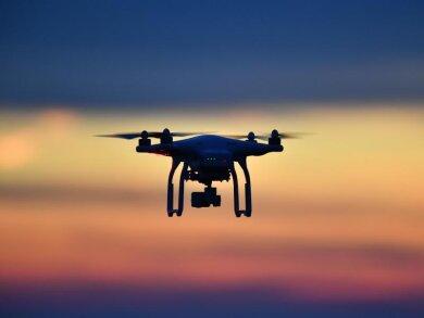Eine Drohne fliegt bei Sonnenuntergang über eine Wiese.