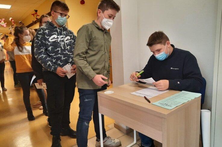 Schlange stehen zur Stimmabgabe: Bei der Juniorwahl im Regenbogen-Gymnasium Augustusburg kontrolliert Wahlhelfer Linus Hönig die Wahlbenachrichtigungen und gibt die Stimmzettel heraus.