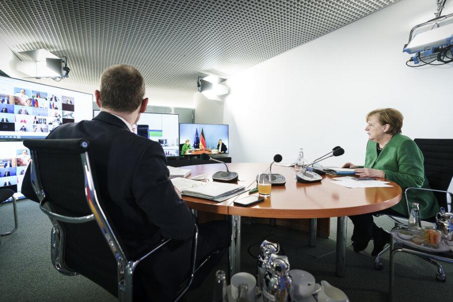 Bundeskanzlerin Angela Merkel (CDU) und Michael Müller (SPD), Regierender Bürgermeister von Berlin, sitzen zusammen während einer Videokonferenz mit den Ministerpräsidenten der Länder zum weiteren Vorgehen in der Corona-Pandemie.