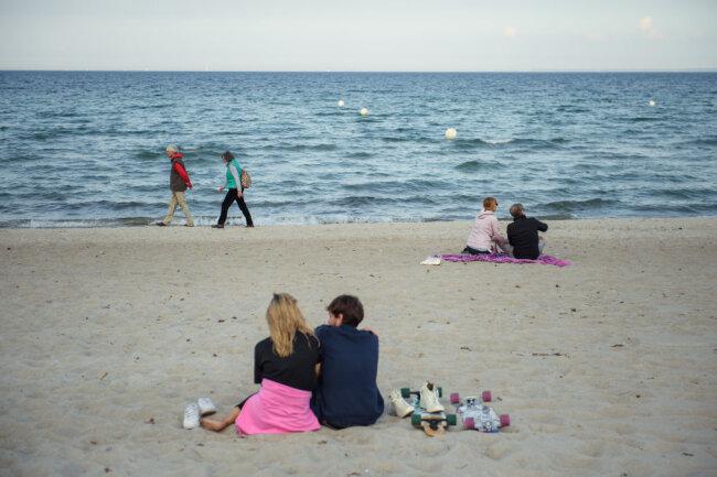 Schleswig-Holstein, Scharbeutz: Paare sitzen und gehen in einigem Abstand zueinander am Strand der Gemeinde Scharbeutz im Kreis Ostholstein.