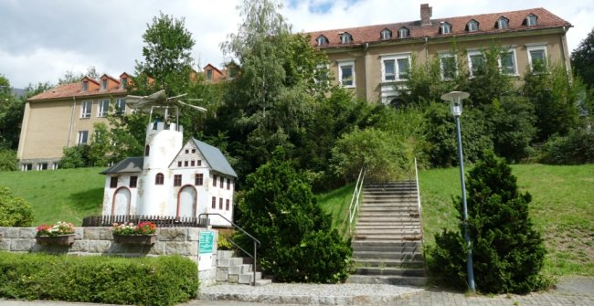Die Treppe hinauf zur ehemaligen Scharfensteiner Schule ist seit Jahren zugewachsen. Weiterhin genutzt wurde jedoch der Pyramidenstandort vor dem Gebäude. Dies soll im Zuge eines Pachtvertrags auch künftig der Fall sein.