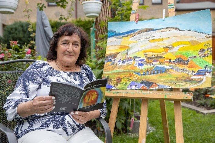 Monika Rüth in ihrem kleinen Garten in Hammerunterwiesenthal mit ihrem Gedichtband und einem Acrylbild, das nach einer historischen Aufnahme von ihrem neuen Heimatort entstanden ist.