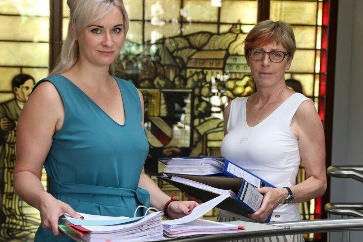 Denise Spindler und Sachbearbeiterin Sabine Marschall mit kompletten Aktenordnern, die sich um eine Person drehen.