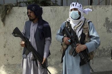 Taliban-Kämpfer stehen am Haupttor zum Präsidentenpalast Wache.