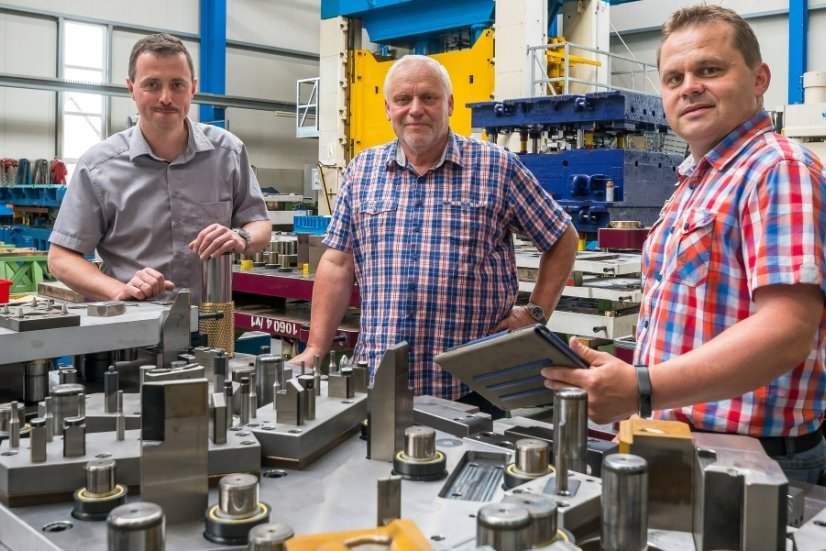 Matthias Oertel (Mitte), der die Geschäftsführung an seinen Sohn Daniel Oertel (rechts) und Ralf Talke übertragen hat, schaut sich mit seinen Nachfolgern in der Produktionshalle ein sogenanntes Folgeverbundwerkzeug zur Herstellung von Motorhaubenscharnieren an.