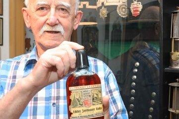 """Jürgen Schlosser in seiner Plattenbauwohnung in Eckersbach. Überall """"Bergbau"""", wo man auch hinschaut. Er zeigt die kleine Flasche """"Echter Zwickauer Koks"""", die er jetzt neu in seiner Sammlung hat."""