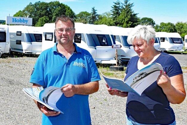 Thomas und Sandra Scheibe vom Caravanzentrum Spitzner in Schönfels haben derzeit Reisemobile lediglich zum Anschauen in Prospekten. Die Wohnanhänger im Hintergrund gehen kommende Woche alle vom Hof.