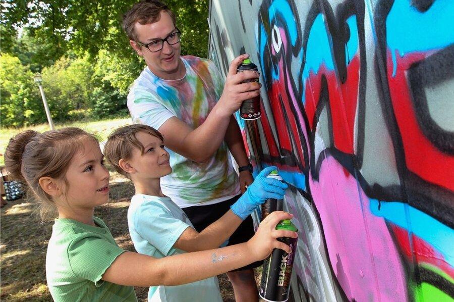 Max Kagerer, Erzieher an der Karl-Marx-Grundschule, teilte in einem Graffiti-Workshop sein Hobby mit Kindern - hier Lisa Becher (7) und Hannes Hofmann (9).