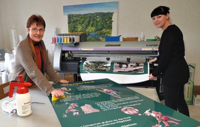 In der Werkstatt der Eibenstocker Grafikdesignerin Ina Gläser (li.) sind die Informationstafeln für den Bergbaulehrpfad in Eibenstock entstanden. Beim Aufziehen hilft ihr Mitarbeiterin Kerstin Kluge.