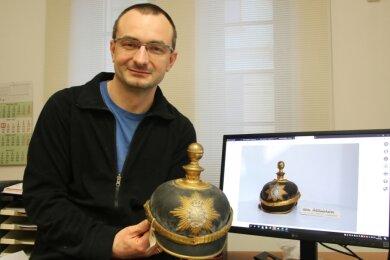Diese mehr als 100 Jahre alte Pickelhaube, die Museumsleiter Michael Heuck hier zeigt, hat es bereits in die digitale Ausstellung geschafft.