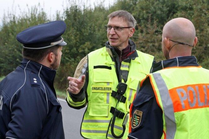 Einsatzleiter Dirk Werner (Mitte) von der Freiwilligen Feuerwehr Gersdorf stimmt mit den Polizisten die Maßnahmen nach der Bergung ab.