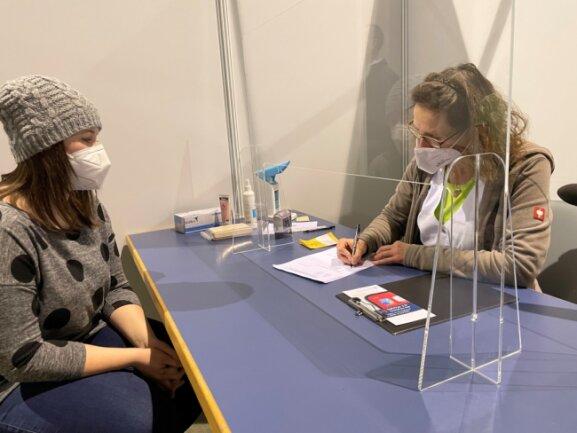 """Franziska Pecher-Werner (rechts), Allgemeinmedizinerin aus Eibenstock, klärte Pflegedienstmitarbeiterin Jennifer Näbelung über die Impfung auf. Anschließend wurde der 24-jährigen Crimmitschauerin der Impfstoff in den Arm gespritzt. """"Es tat gar nicht weh"""", sagte Näbelung."""