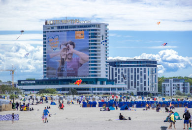 Ein 40 mal 40 Meter großes Plakat hängt am wegen der Corona-Schutzmaßnahmen geschlossenen Hotel Neptun und wirbt für ein nachhaltig gutes Tourismusklima in Mecklenburg-Vorpommern. Die Hotels in Mecklenburg-Vorpommern dürfen wieder alle Betten belegen.