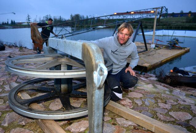 Jens Geißler von der Firma Wake-Concept begutachtet an der Wasserskianlage Rossau eine der Umlenkrollen, über die dann das Seil läuft.