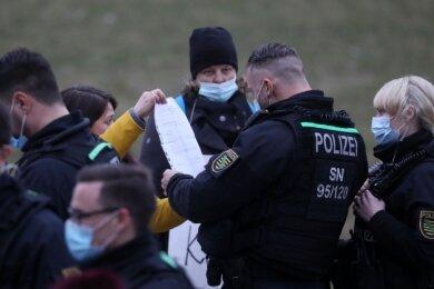 Polizeibeamte werfen einen Blick auf Atteste, die einige Demo-Teilnehmer in Waldenburg vorlegten.