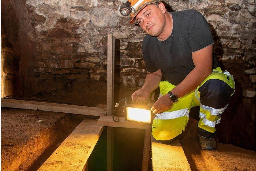 Steiger Sven Meyer von der Bergsicherung Sachsen leuchtet in den Kriechgang, den das Unternehmen im Keller unter dem Schillinghaus freigelegt hat. Ein Gitterrost soll diesen künftig sichern.